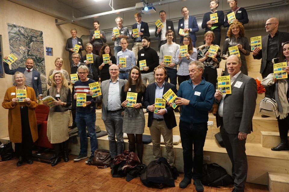Met Ruimte en Wonen in de hand op de foto bij Live-bijeenkomst op 13 december in Zwolle